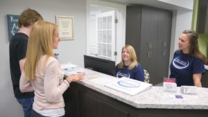 Team Demas front desk administrator talking to a patient and his mom